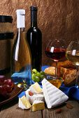 Supper consisting of Camembert and Brie cheese, honey, wine and grapes on napkin in basket and wine barrel on wooden table on brown background