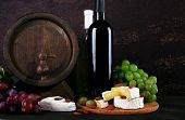 Supper consisting of Camembert cheese, wine and grapes on cutting board and wine barrel on wooden table on brown background