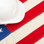 White Color Construction Helmet Laying Over Us Flag