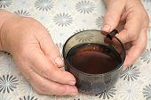 Old Hands Holding A Cap Of Tea