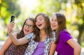 Happy Teen Girls Taking Selfie In Park