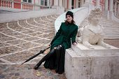Woman in a green coat posing on stairs