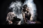 stock photo of crawling  - Two male zombies crawling on their knees on black smoky background looking at camera - JPG