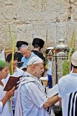 JERUSALEM, ISRAEL - SEPTEMBER 20, 2013: The Western Wall of the Temple in Jerusalem. Many religious Jews in traditional white robes tallit gathered for prayer. Morning Sukkot