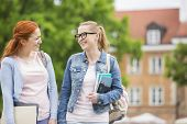 Happy young female college friends walking outdoors