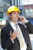 Man In Industrial Hard Hat And Talking On Cell Phone