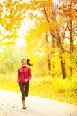Athlete runner woman running in fall autumn forest. Female fitness girl jogging on path in amazing fall foliage landscape nature outside.