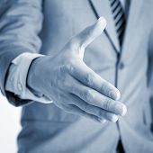 Close up businessman offer hand shake, in blue toned effect.
