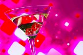 Red Dice In The Cocktail Glass On Blur Pink Background