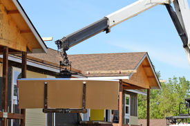 pic of boom-truck  - A special truck mounted lift truck or crane is used to move drywall into a two story commercial residential building - JPG