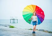 Outdoor portrait of a cute little girl with colorful umbrella under the rain