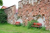 Red benches by medieval 13th century brick ruin