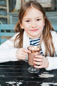 Little girl drinking hot chocolate in cafe