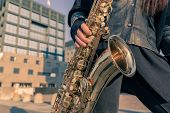 stock photo of saxophones  - Detail of a woman posing in the city streets with her saxophone - JPG