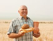 stock photo of loamy  - successful agriculturist with different baking foods and jug - JPG