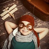 stock photo of little boys only  - Top view of happy little boy in pilot headwear and eyeglasses lying on the hardwood floor and smiling while wooden planer and briefcase laying near him - JPG