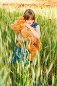 Summer portrait of a cute little girl playing with teddy bear