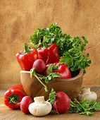 Mix vegetables (tomatoes, cucumbers, mushrooms, herbs) on a wooden table