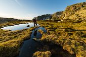 image of meter stick  - Male hiker with backpack and stick taking rest and watching sunrise near lake and stream in the italian Alps - JPG
