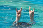 Two Hands Out Of Water In Rock Gesture