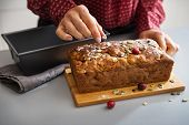 Closeup On Young Housewife Decorating Freshly Baked Pumpkin Bread With Seeds