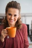 Portrait Of Happy Young Housewife Drinking Tea In Kitchen