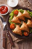 foto of samosa  - Indian samosa delicious pastry on a plate on a wooden table closeup - JPG