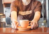 Barista Offering Orange Cup Of Coffee