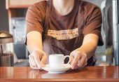 Barista Offering Mini White Cup Of Coffee