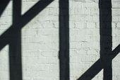 Strips shadow on bricks wall.