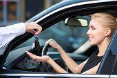 Car dealer giving keys to happy woman