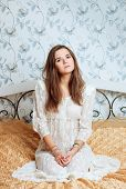 Young dreamy brunette woman in vintage lace boho dress sitting on the bed