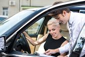 image of contract  - Car dealer and happy smiling woman signing a contract. Concept for car rental