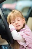 Little girl sleeping on car steering wheel