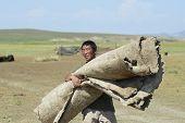 Mongolian man carries felt circa Harhorin, Mongolia.