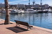 image of costa blanca  - Wooden bench at the bank of the Alicante harbour, Costa Blanca, Spain. Yachts and hotels at the background