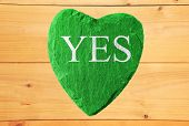 green heart with yes writing and wooden background