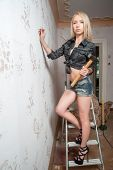 Attractive blond woman with hammer and screw