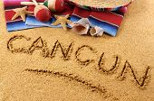 foto of mexican fiesta  - The word Cancun written in sand on a Mexican beach with sombrero straw hat traditional serape blanket starfish and maracas - JPG