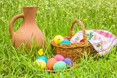 Easter Eggs, Basket And A Jug In The Grass