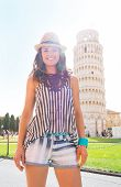 Portrait Of Happy Young Woman Standing In Front Of Leaning Tower Of Pisa, Tuscany, Italy