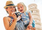 Portrait Of Happy Mother And Baby Girl Checking Photos In Camera In Front Of Leaning Tower Of Pisa,