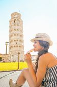 Happy Young Woman Eating Pizza In Front Of Leaning Tower Of Pisa