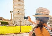 Young Woman Taking Photo Of Leaning Tower Of Pisa, Tuscany, Italy. Rear View