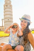 Happy Mother And Baby Girl Taking Photo In Front Of Leaning Tower Of Pisa, Tuscany, Italy