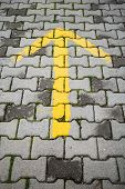 Yellow Arrow On Gray Cobblestone Pavement
