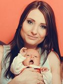 Happy Mother Holding Newborn Baby Girl In Arms