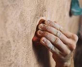 Man climbing on wall in gym, close-up of hand