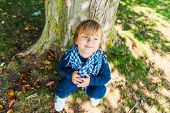 Close up portrait of a cute toddler boy resting under the tree on a nice sunny day