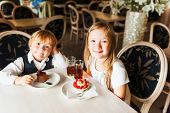 Adorable children eating cakes in a beautiful cafe